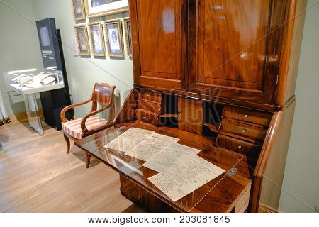 Ostafyevo, Moscow region - May 13, 2017 - Part of cabinet in old mansion 18-19 centuries. Bureau, armchair, paintings, sculpture. Old furniture from Karelian birch.