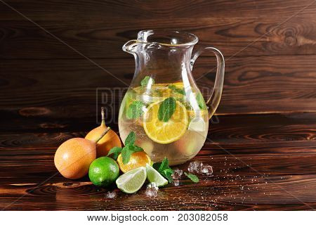 Fancy glasses of liquor or rum with fresh citrus fruits on a dark wooden background. A jar of alcoholic exotic beverage with spicy mint and ice. Refreshment and relax at the bar concept. Copy space.