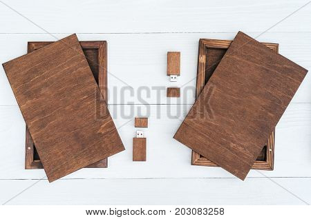 Empty blank wooden boxes for gift or photos with usb stick free space. Packaging for photo and USB drives on white wooden background. Information and mail concept