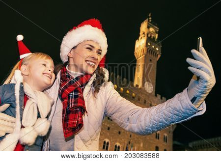 Mother And Daughter In Christmas Hats Taking Selfie In Florence