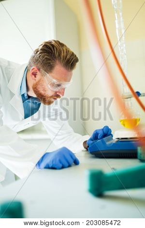 Attractive male student of chemistry working in lab