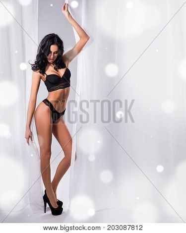 Winter Concept - Full Length Portrait Of Beautiful Woman In Black Lace Lingerie Posing Behind White