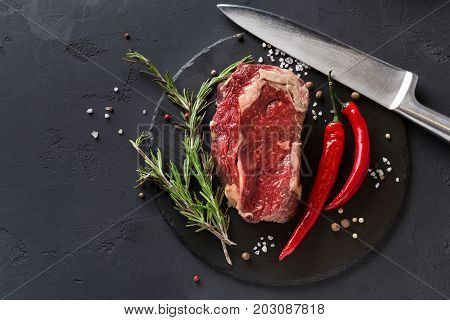 Raw rib eye steak with herbs. Cooking ingredients for restaurant dish. Fresh meat with chilli and knife on plate on black background, copy space, top view