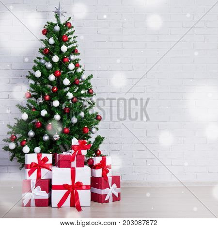 Decorated Christmas Tree With Colorful Balls And Gift Boxes Over White Brick Wall And Snowfall