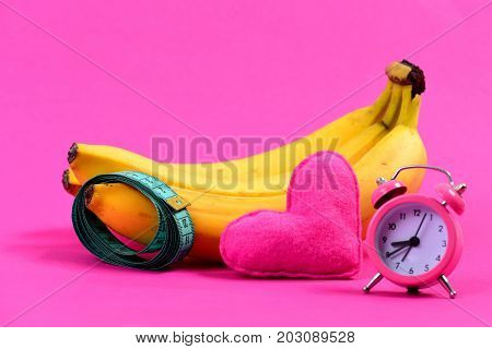 Roll Of Measuring Tape And Bananas Near Heart And Alarm Clock