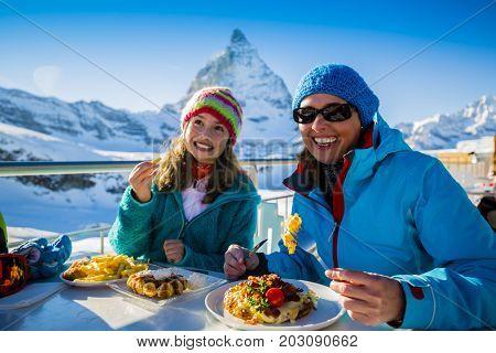 Winter ski holidays - skiers enjoying break for lunch, mountain view Matterhorn