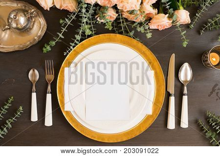 Tableware - set of plates and utencils with flowers on wooden table
