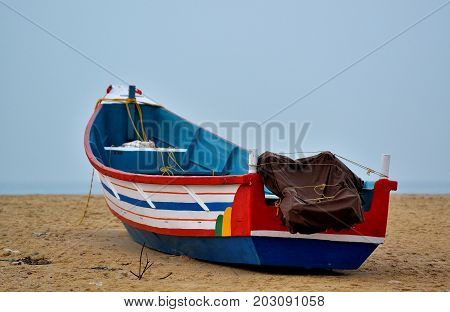 Traditional colorful wooden boat on sand beach, India