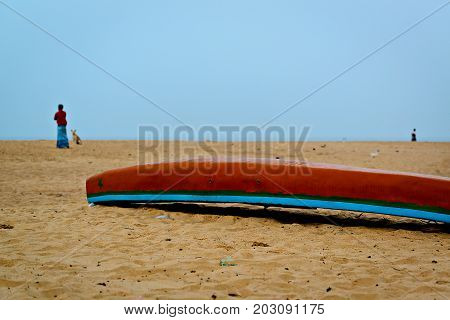 Traditional fishing boat turned upside down on a beach with woman and dog figures in background