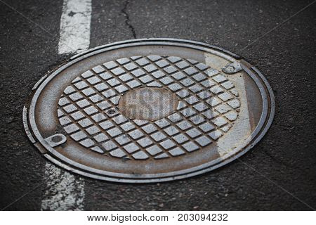 Rustic, metal, vintage, retro, old, cracked hatchway with a geometrical ornament on a gray pavement road background. Dirty hatchway on the road surface closing canalization with sewerage.