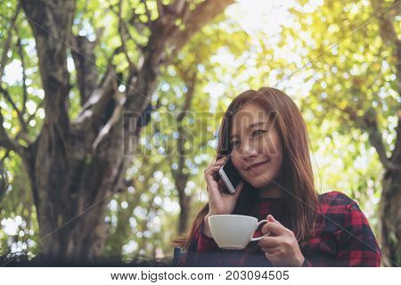 Closeup portrait image of a smiley beautiful Asian woman holding and talking on smart phone at outdoor while drinking coffee with green nature background