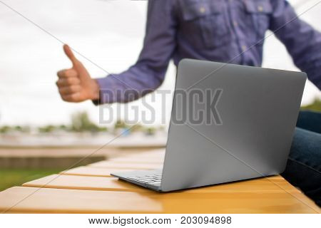 Close-up picture of light gray wireless, modern laptop on a bench on a blurred park background. Young man giving a thumb up to a laptop. A programmer using electronics. Copy space.