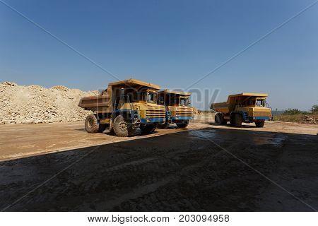 Tipper or dumper trucks, dump trucks in a sand quarry, transporting of sand, gravel, demolition waste on a natural background.
