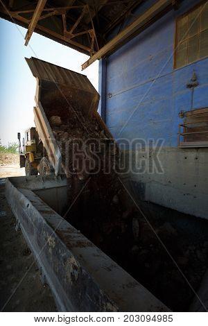 Tipper or dumper truck, dump truck unloads stones in a sand quarry, transporting of sand, gravel, demolition waste on a natural background.