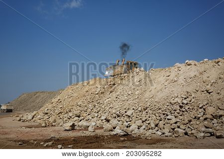 A digger, a loader backhoe, a bachoe loader on a pile of sand and stones, a heavy equipment vehicle, construction, light transportation of building materials, powering building equipment on a natural background.