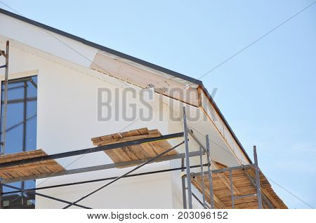Corner of house with eaves rafters truss. Install softies and roof insulation detail. Roofing.