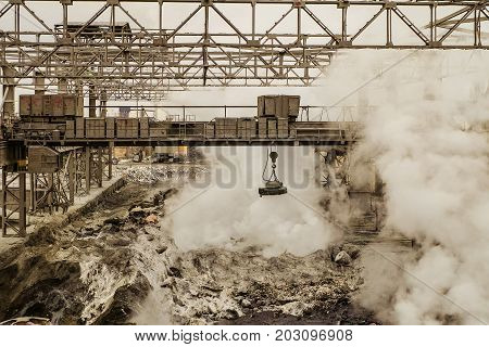 Metallurgical hot slag dump with magnetic overhead crane. Mining heavy industrial background.