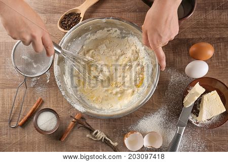 Woman making dough for vanilla cake in kitchen