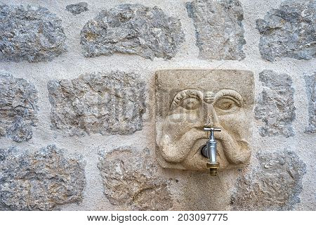 Perast Montenegro. Old town carved stone head as a water crane on the ancient stone wall. Copy space for your text. Water consumption concept.