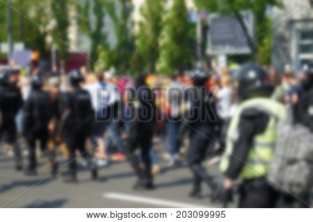 Blurred view of crowd and police on city street