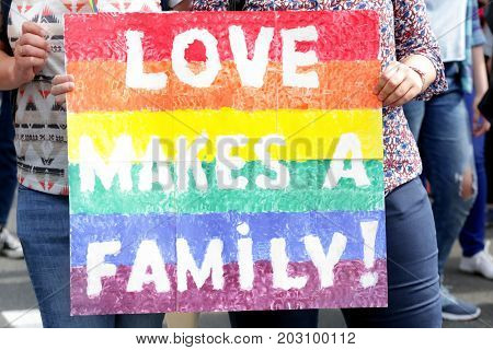 Concept of sexual minority. Woman holding poster with text LOVE MAKES A FAMILY during gay parade outdoors