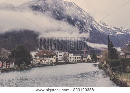 Landscape of small village in winter with big mountain and mist layer in Interlaken at western Switzerland, Scenery of beautiful waterfront village in Interlaken with Alps Mountain over the mist, View of curve canal with folk village and foggy mountain