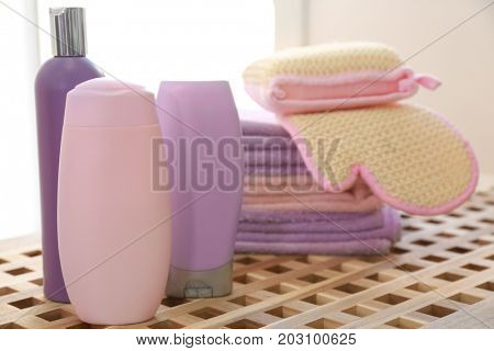 Composition with bath cosmetics and accessories on wicker table