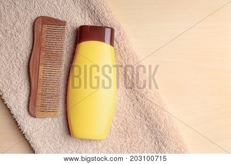 Bottle with shampoo and comb on wooden background