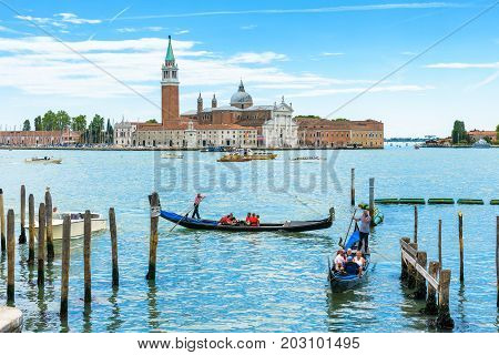 Venice, Italy - May 21, 2017: Gondolas with tourists are sailing along the Venetian lagoon. San Giorgio Maggiore in the background. The gondola is the most attractive tourist transport in Venice.