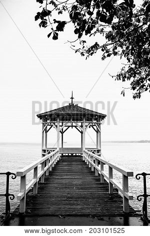lonely pier and boardwalk at lake constance black and white