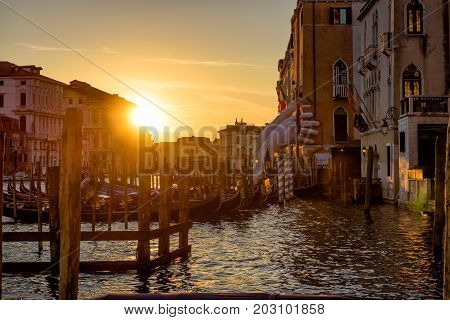 Venice, Italy - May 18, 2017: Grand Canal with a pier for gondolas at sunset. Giant hands supporting the building are a sculpture by the artist Lorenzo Quinn.