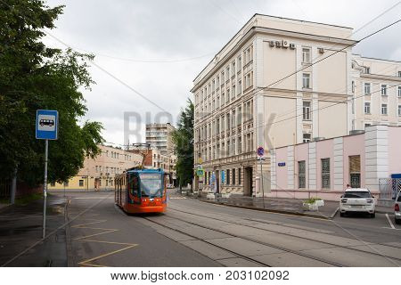 MOSCOW RUSSIA - JULY 17 2017: MIIT Humanitarian Institute (right) and tram in Obraztsova Street. Obraztsova Street is located in North-Eastern Administrative District of Moscow.