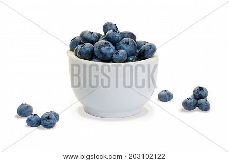 Closeup blueberry in white ceramic cup and small piles of blueberry on white background isolated