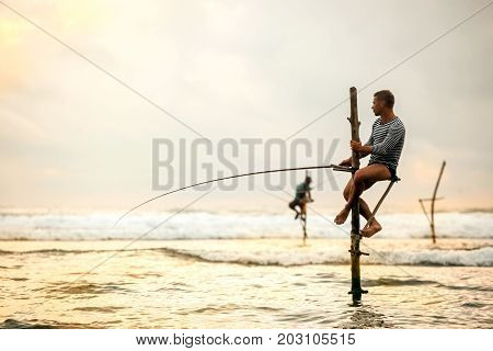 The European tourist is engaged in traditional fishing on poles in the Indian Ocean. Sri Lanka.