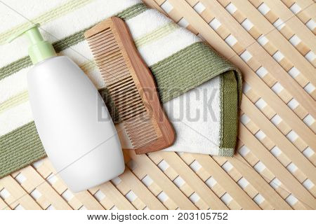 Bottle with lotion and comb on towel