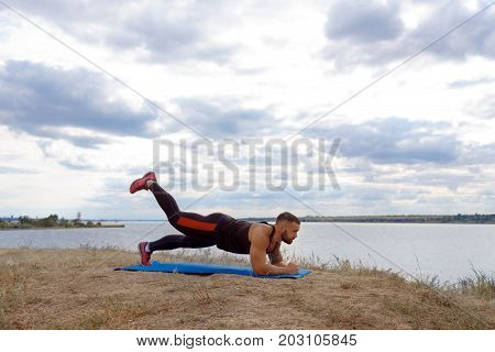 A strong muscular bodybuilder with a tattoo on his shoulder standing in a plank on a blurred natural background. Workout, fitness, routine, training concept.