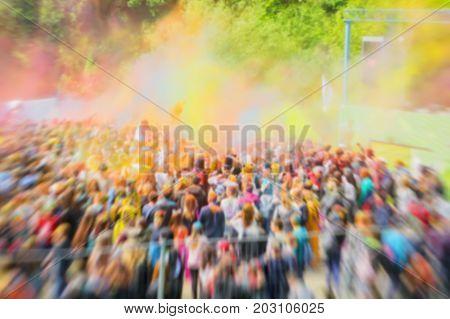 Blurred unrecognizable happy young people celebrate Holi festival. Colorful vivid powder explosion