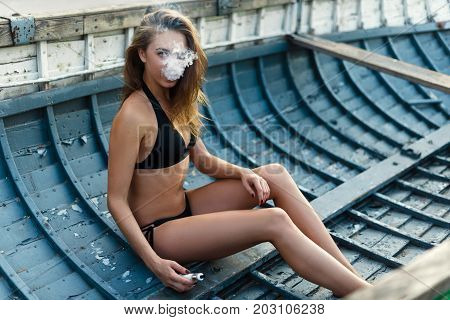 Vapor Concept,sexy Young Woman In Swimsuit Vaping And Sitting In Old Wooden Boat
