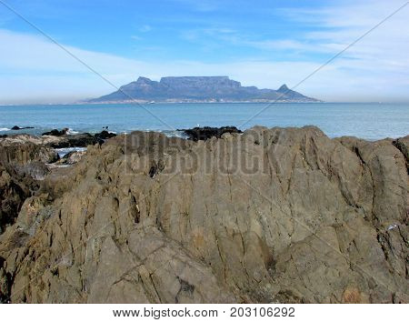VIEW FROM BLOUBERG STRAND, CAPE TOWN, SOUTH AFRICA, WITH HUGE BOULDERS IN THE FORE GROUND AND TABLE MOUNTAIN IN THE BACK GROUND 40ch
