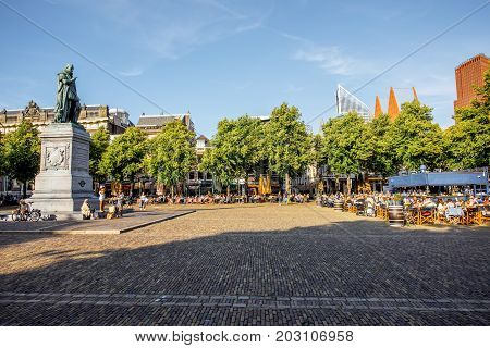 HAAG, NETHERLANDS - August 06, 2017: View on the Plein square with statue of William and modern skyscrapers on the background during the sunset in Haag city