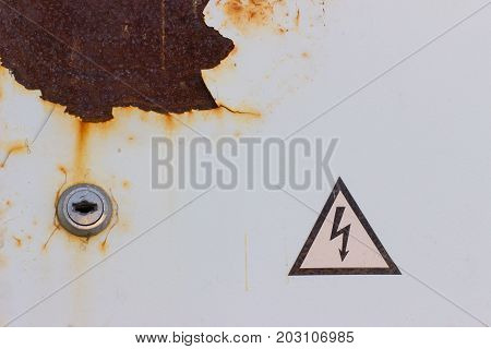 """colored white metal in corrosion and rust with the sign """"carefully high voltage"""" poster"""