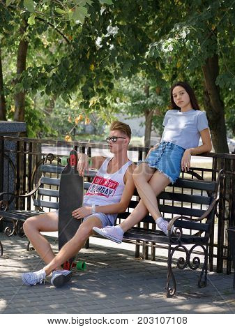 A beautiful girl sitting with a fellow on a bench in a park, dating in a park on a blurred natural background. Love, date, dating, outdoor, park, nature concept.