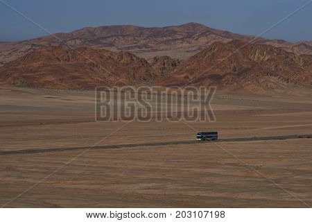 Atacama Desert, Chile - August 18, 2017: Long distance coach on the Pan American Highway (Ruta 5) running through the harsh and arid landscape of the Atacama in northern Chile.