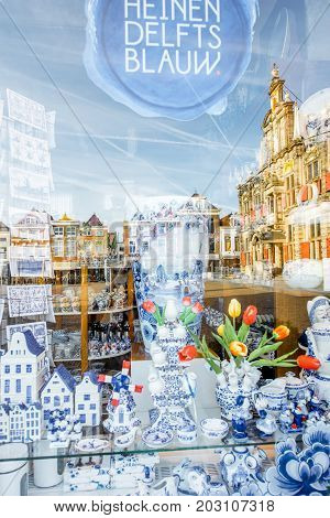 DELFT, NETHERLANDS - August 07, 2017: Store showcase with famous dutch traditional blue porcelain with reflection of Delft city in Netherlands