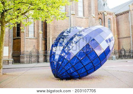 DELFT, NETHERLANDS - August 07, 2017: Blue Heart sculpture in Delft, Netherlands. The sculpture was placed in 1998 and created by Marcel Smink, the sculpture is made out of glass and steel