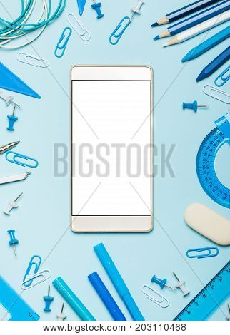 School supplies of blue and white colors on a blue background and the phone. Modern necessary school things. Male or boyish still life on the topic of school, study, office work. Flat lay