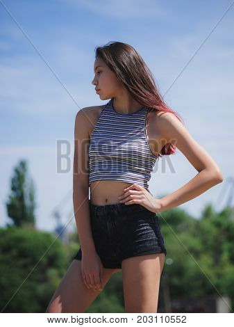 A close-up portrait of an attractive young hipster girl wearing a striped T-shirt and black shorts on a blurred natural background. A beautiful adolescence lady with long colored hair posing outdoors.