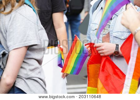 Concept of sexual minority. Woman holding gay rainbow flag outdoors