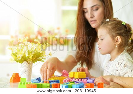 Mother and little daughter playing with colorful plastic blocks