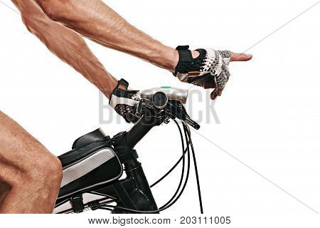 The gloved hand of sportive bicyclist on handlebars shows the direction. white background